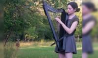 Joven toca el arpa en medio del bosque y atrae a un ciervo con bella melodía