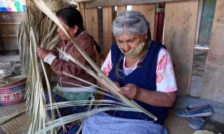 Indígenas oaxqueñas elaboran cubrebocas de palma
