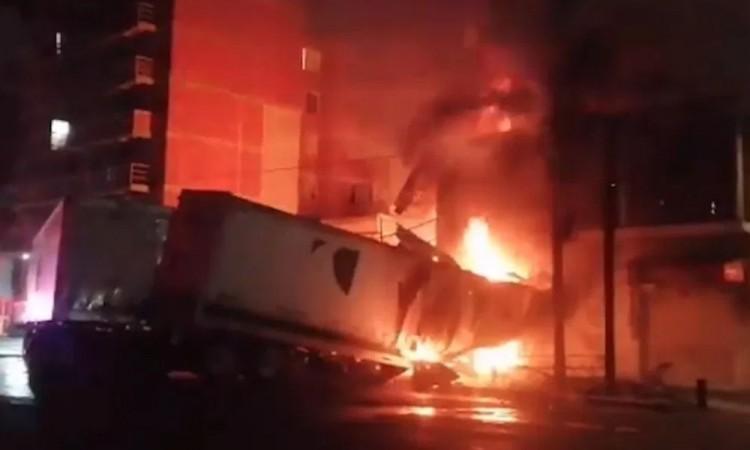 Tráiler contra coche y taller mecánico provocando incendio